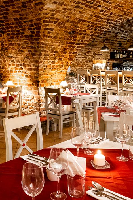 Ciepłe wnętrze restauracji w Krakowie. Restauracja w Dworku BIałoprądnickiego na Prądniku Białym. Cegły na ścianach, czerwone obrusy, świece.