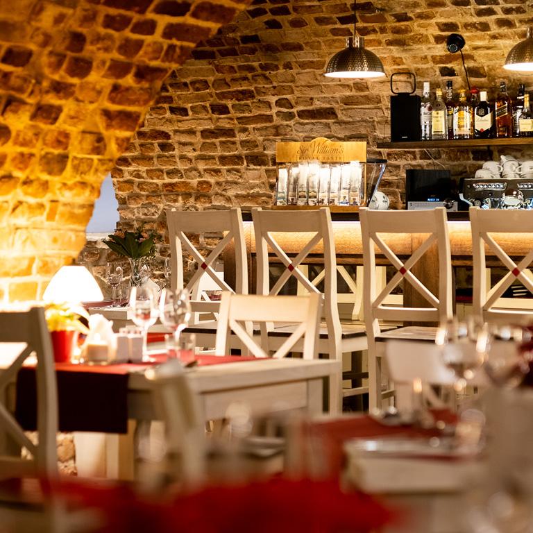 Bar w restauracji Dworek, nad nim stylowe nowoczesne lampy.