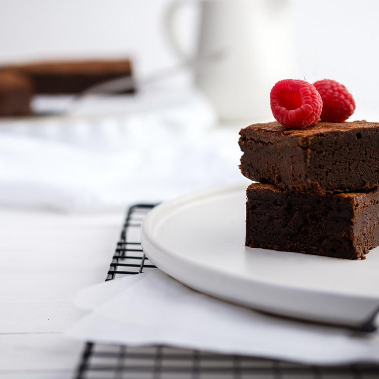 Czekoladowe ciasto brownie ze świeżymi malinami.