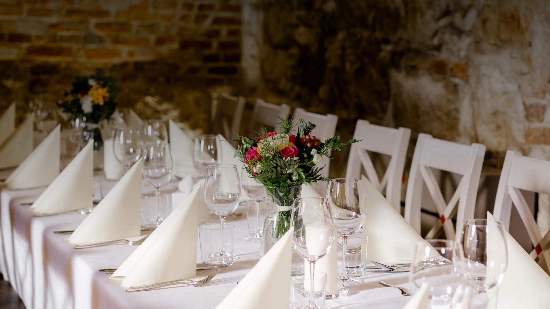 Eleganckie nakrycie stołu na przyjęcie okolicznościowe. Białe obrusy, świeże kwiaty i świece.