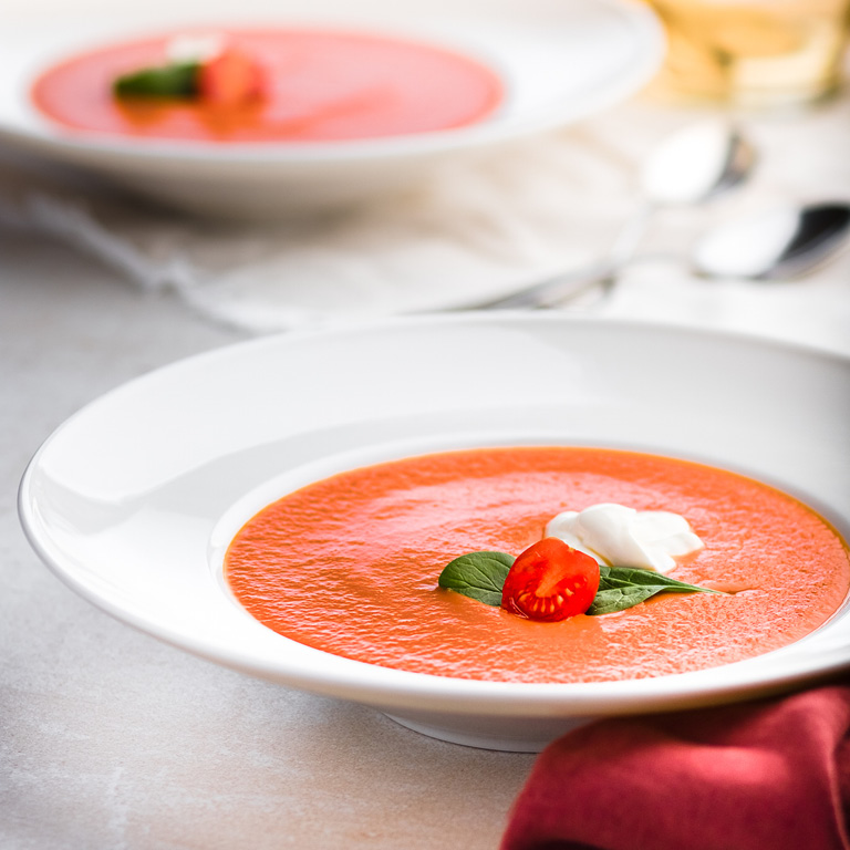 Krem pomidorowy z dekoracją pomidorków koktajlowych, świeżą bazylią i odrobiną śmietany.