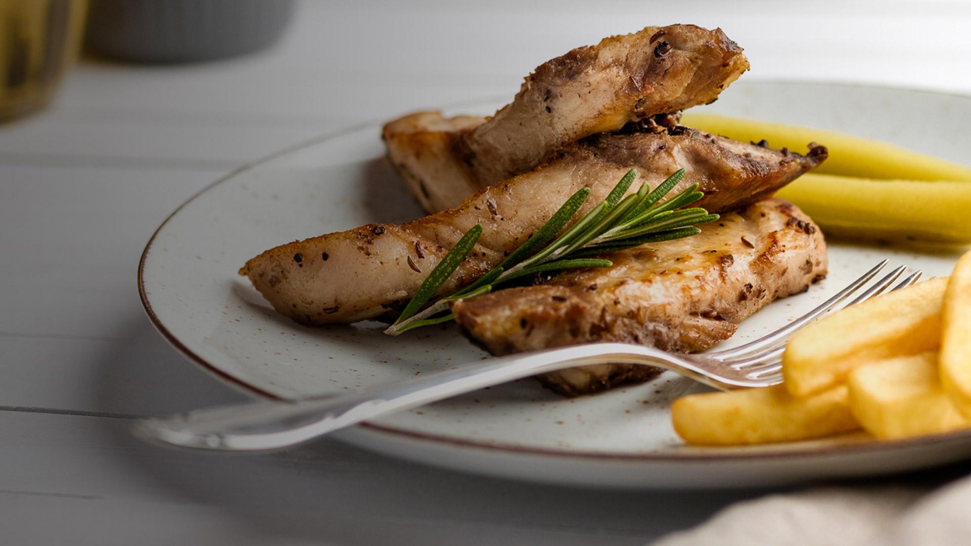 Grillowana pierś z kurczaka z frytkami, zdobiona świeżym rozmarynem.