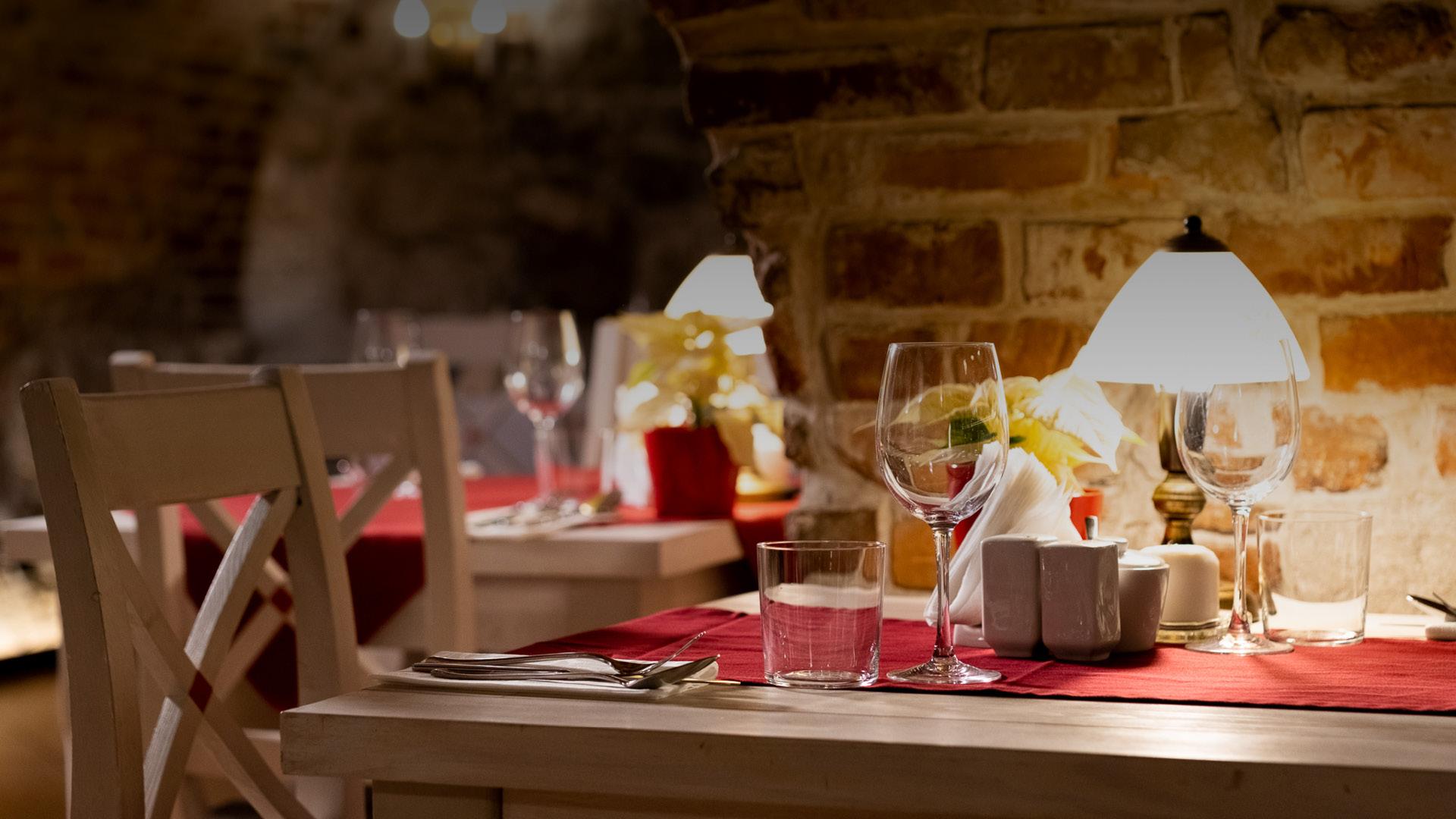 Stolik z czerwonym obrusem, kieliszkiem do wina, szklanką i sztućcami. Piwniczne wnętrze restauracji Dworek.