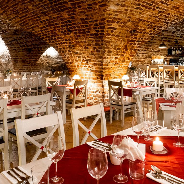 Oświetlona restauracja Dworek, piękne nakrycie stołów. Stylowe wnętrze.