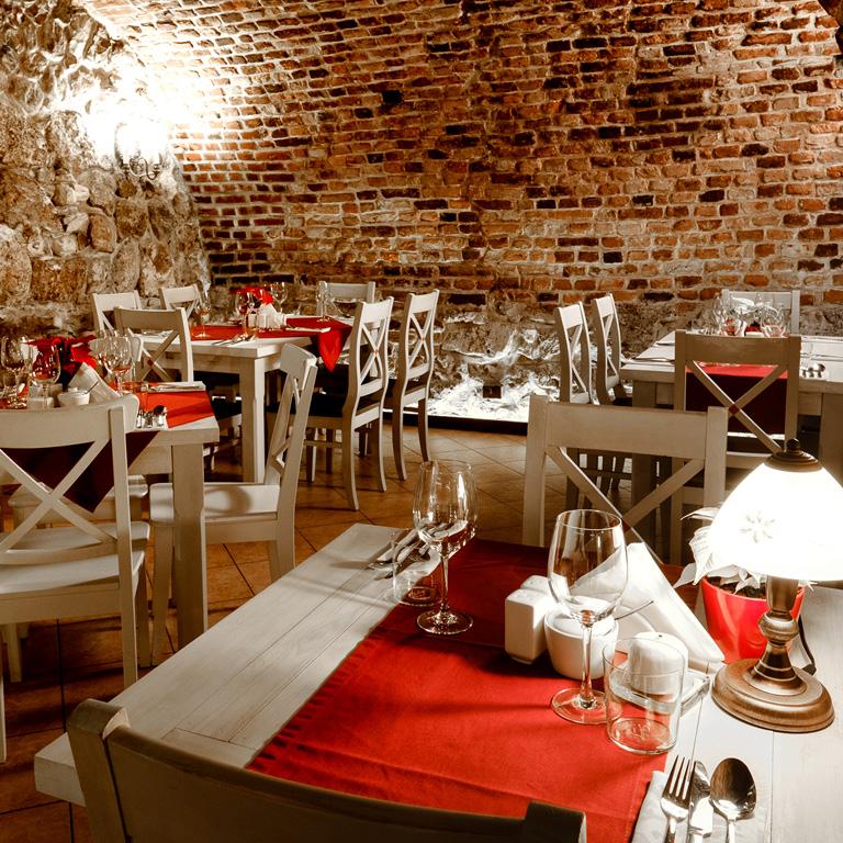 Wnętrze restauracji Dworek w Krakowie. Ceglane ściany, ciepłe oświetlenie, lampki na stołach.