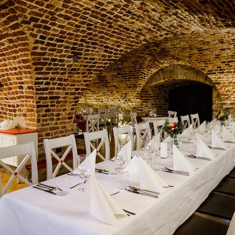 Restauracja Dworek, idealna na przyjęcie okolicznościowe. Nakryty biały stół.