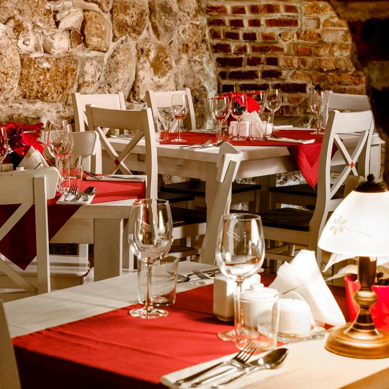 Sala restauracji Dworek na Białym Prądniku. Białe drewniane krzesła i stoły. Bordowe nakrycia.