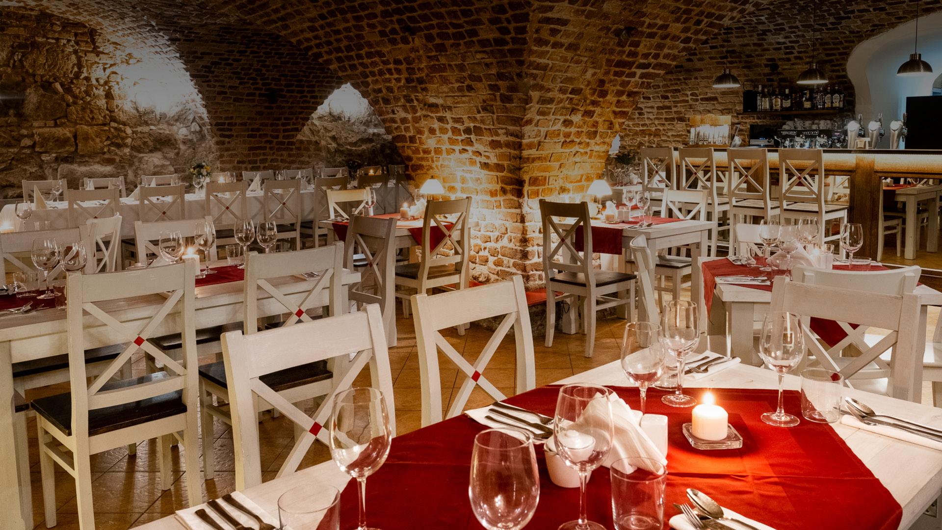 Sala restauracji Dworek w Krakowie. Piwniczna sala z widocznymi cegłami. Na stołach szklanki, kieliszki do wina i świece. Elegancki wystrój