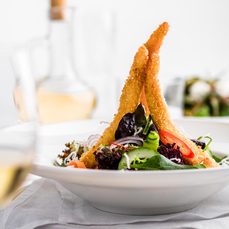 Świeża sałatka z kurczakiem w panierce. Miks świeżych warzyw z zarumienionym kurczakiem.