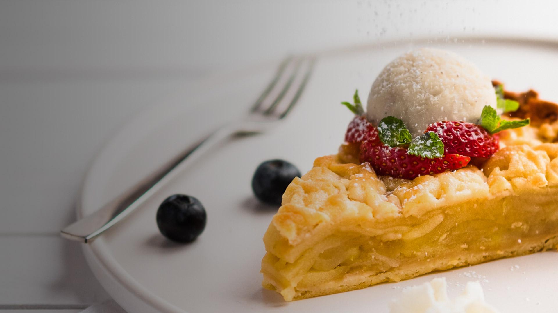Szarlotka z lodami waniliowymi z truskawkami posypana cukrem pudrem.