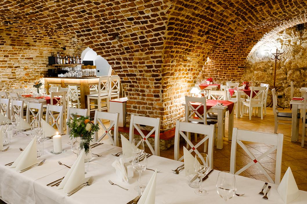 Ułożenie Sali restauracyjnej pod przyjęcie. Białe obrusy, kwiaty, świece. Zabytkowa sala piwniczna z filarem.